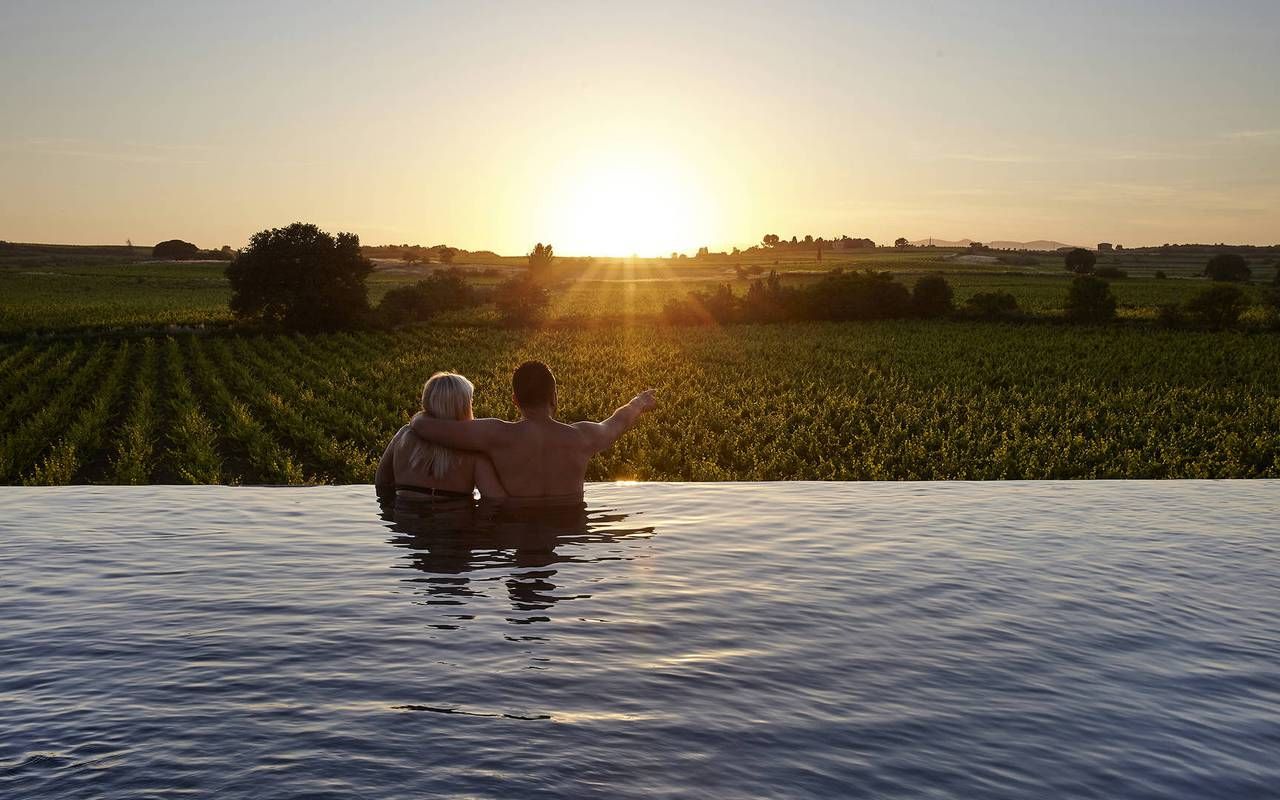 Couple admiring the sunset in the swimming pool, charming hotel in Occitania, Domaine et Demeure